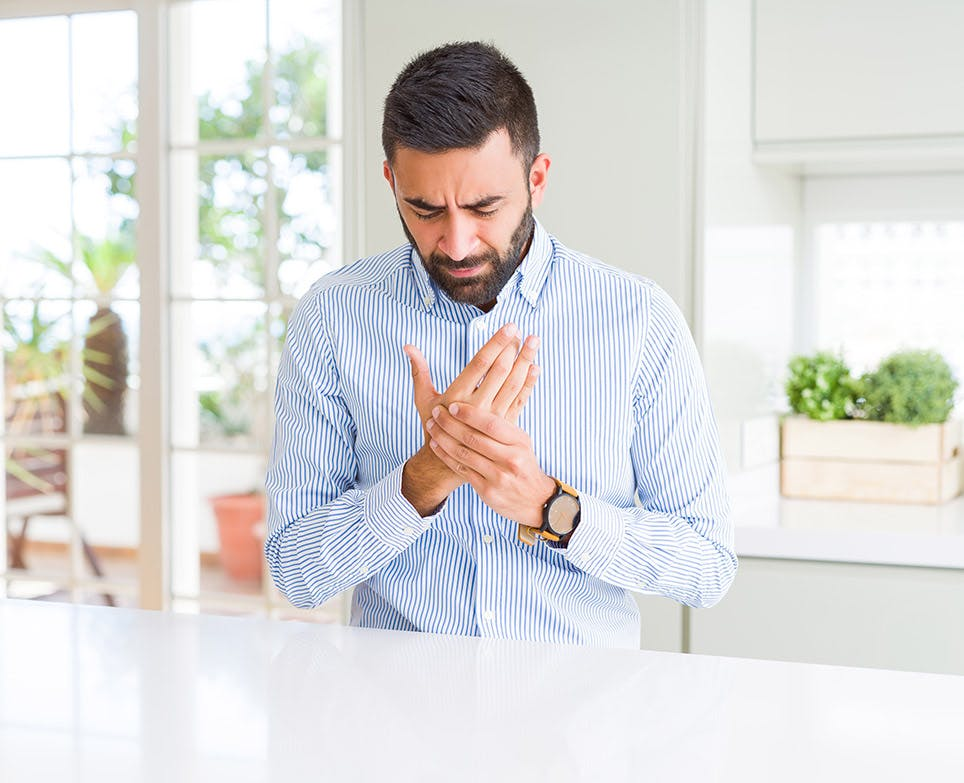 A man experiencing bone pain in his hand
