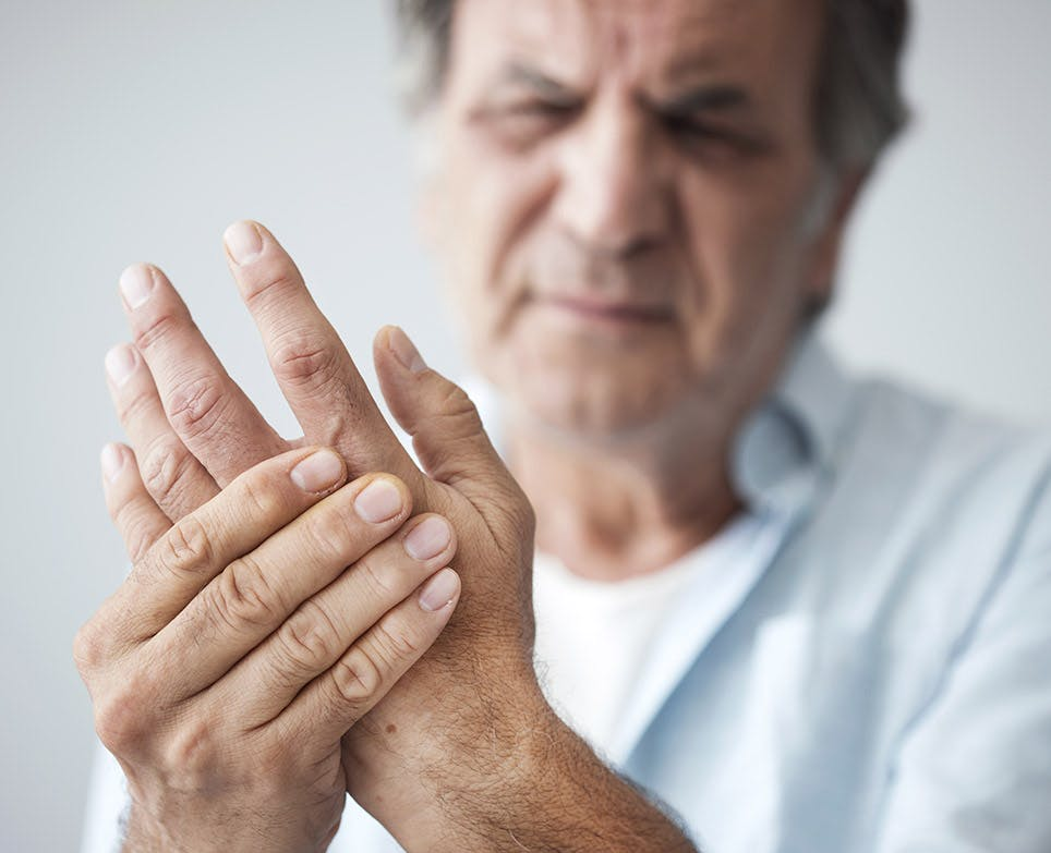 A man handling pain in his left hand