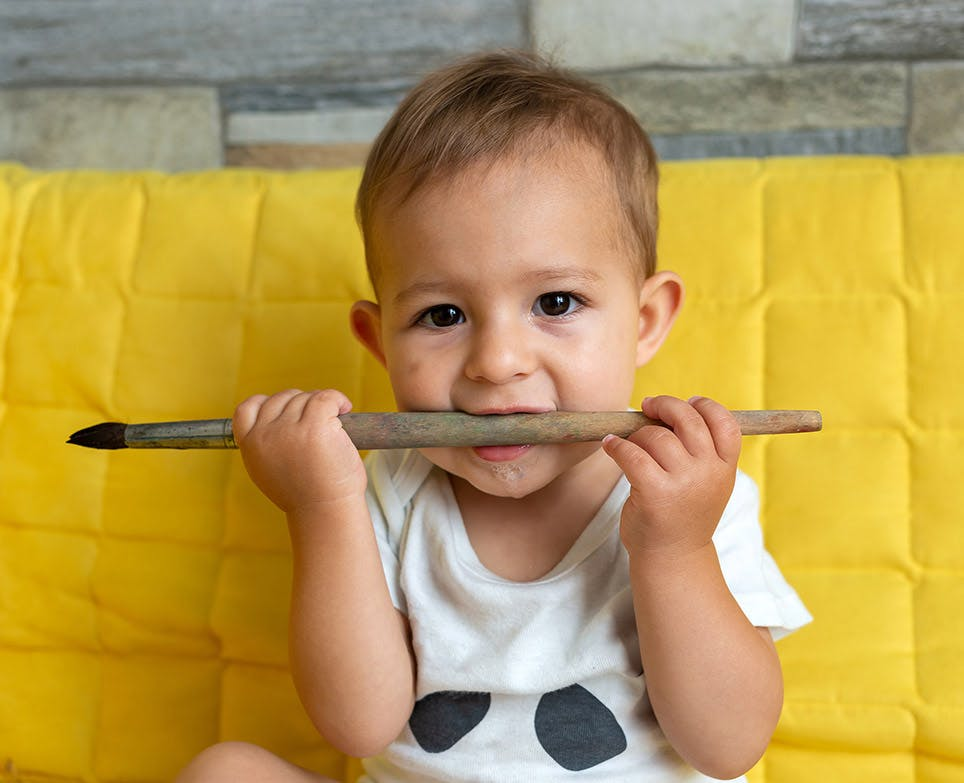 A baby chewing a brush