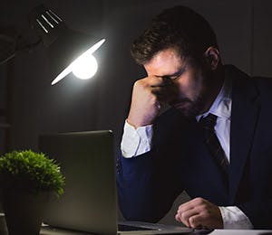 Man in the gloom, grabbing his nose because of a strong headache.