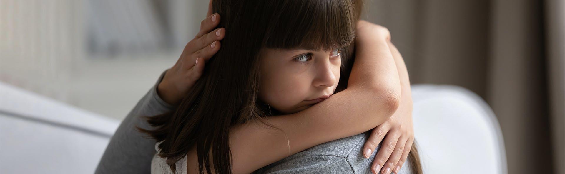Mother hugging her sick daughter.