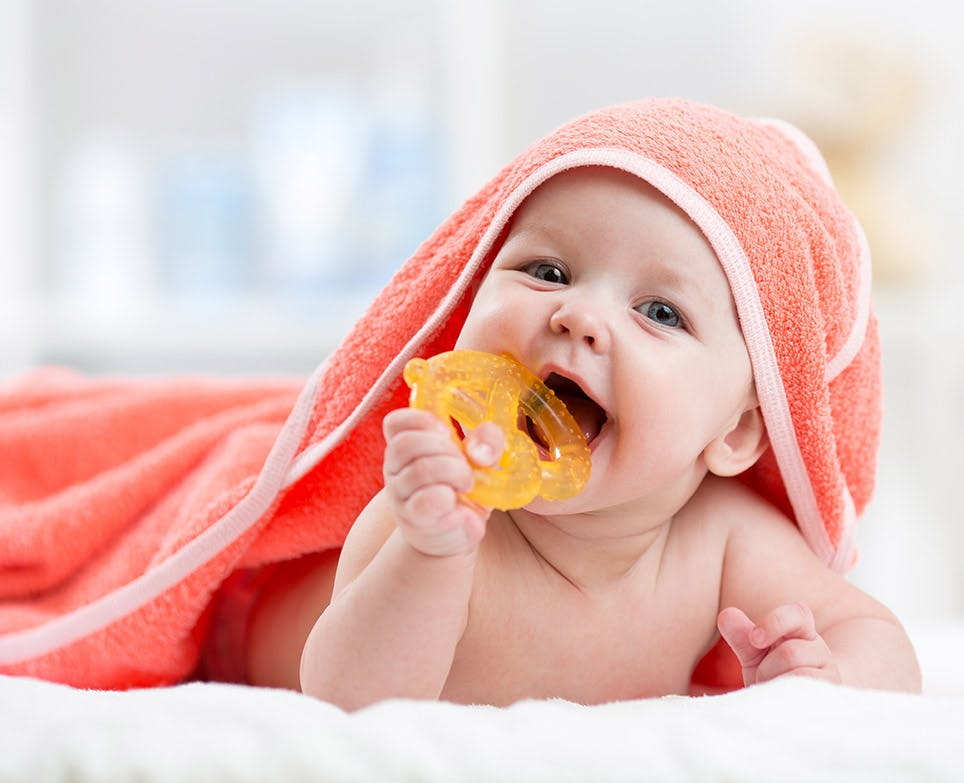 Baby biting a teething toy after a bath.