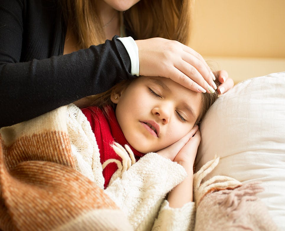 Mother feeling her daughter's temperature by touching her forehead.
