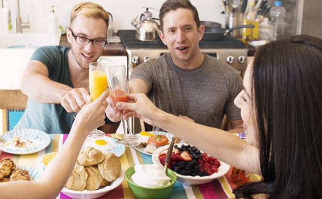 Friends Raise Their Glasses Together In A Toast At Breakfast