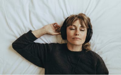 Girl lying on bed with headphones on