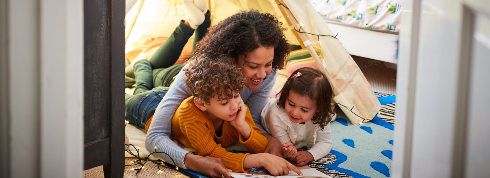 Mum reading a book to her two kids in makeshift tent