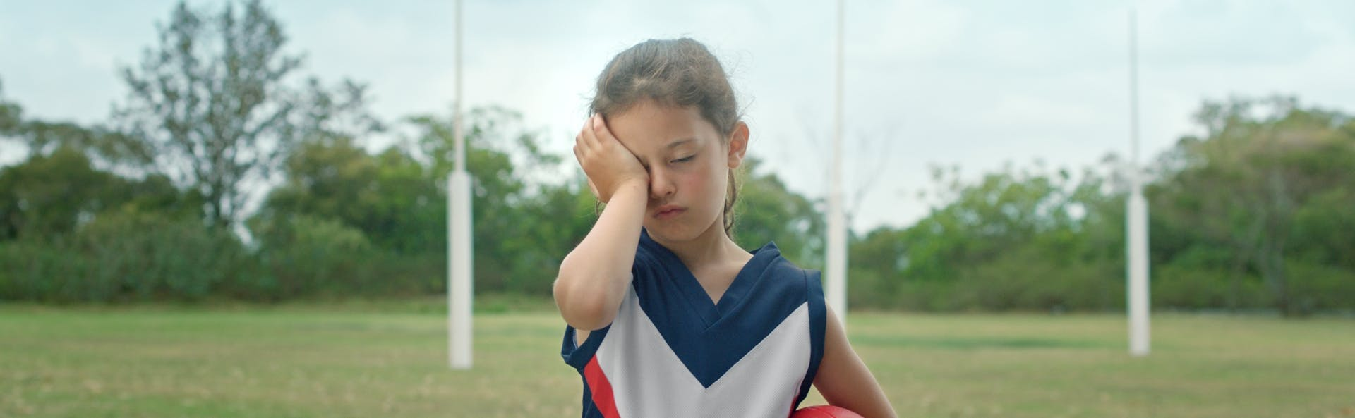Kid in sports clothes rubbing their eye