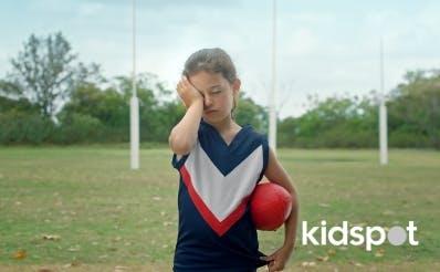 Kid in sports clothes rubbing their eye.