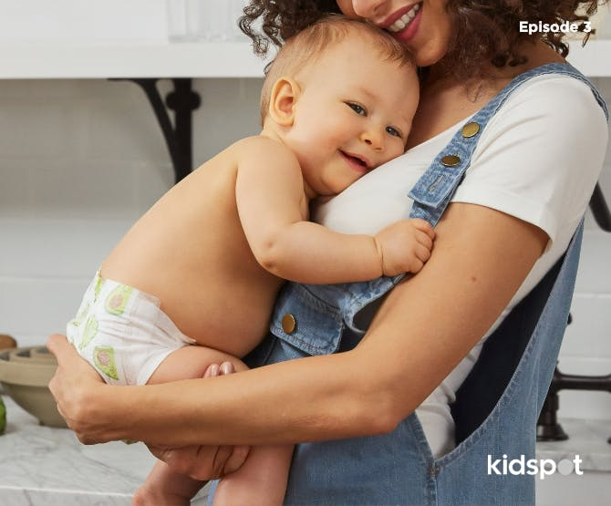 Mother in overalls hugging her baby in nappy