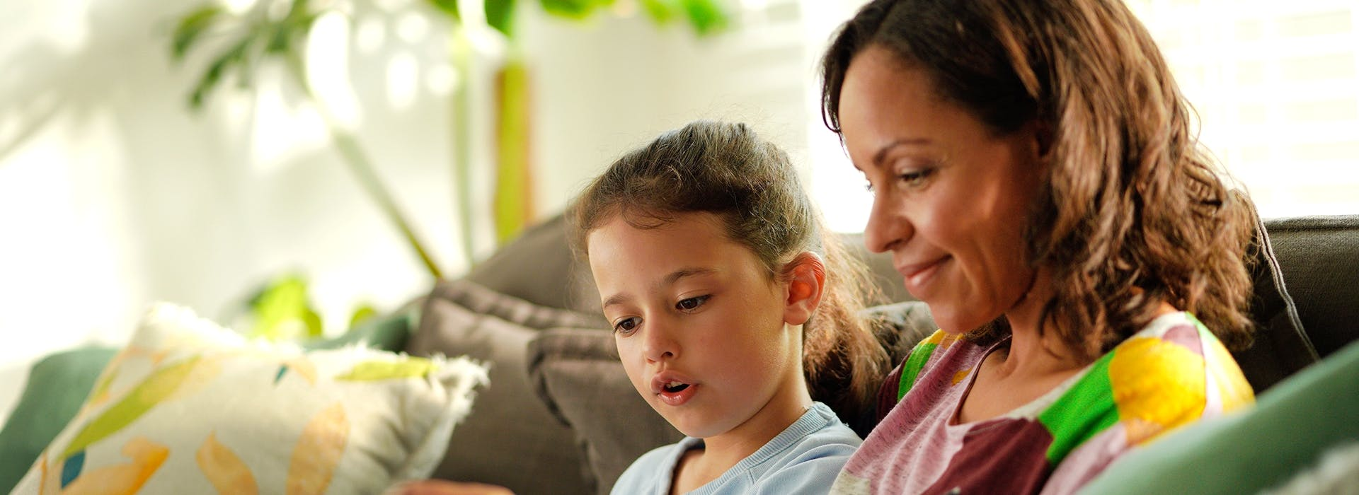 Mum and daughter reading book on couch