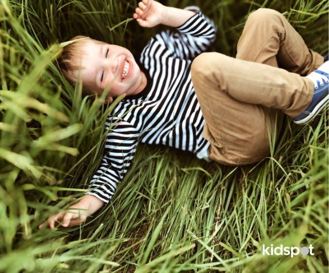 Boy giggling lying in grass