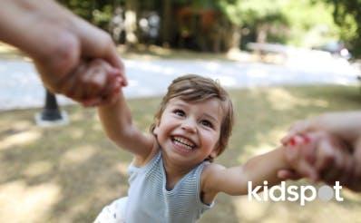 Kid grinning being spun around