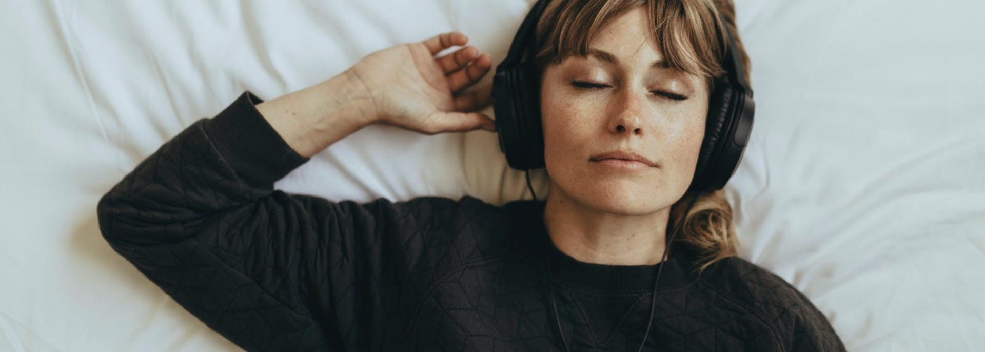 Girl lying on bed with headphones on