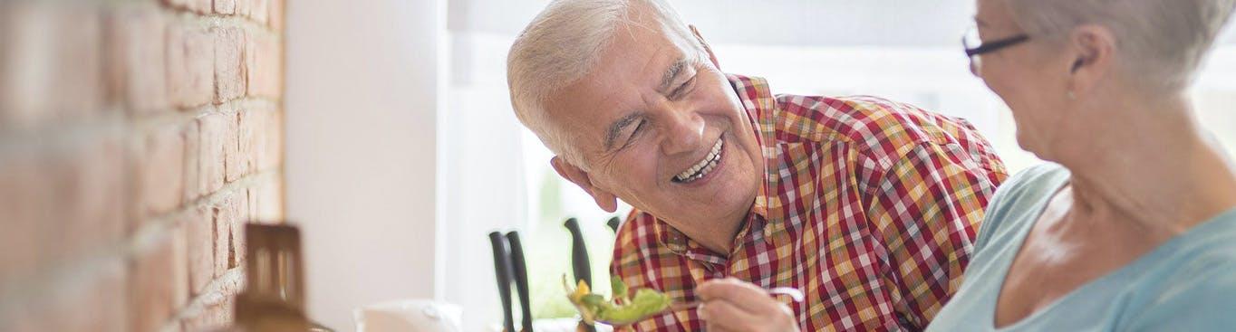 Pareja mayor comiendo ensalada y sonriendo.