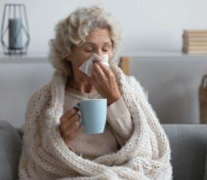 Adulta mayor con congestión nasal, limpiando su nariz y tomando una bebida caliente.