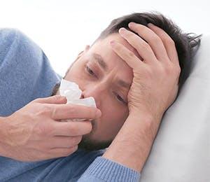 Hombre con síntomas gripales limpiando su nariz.