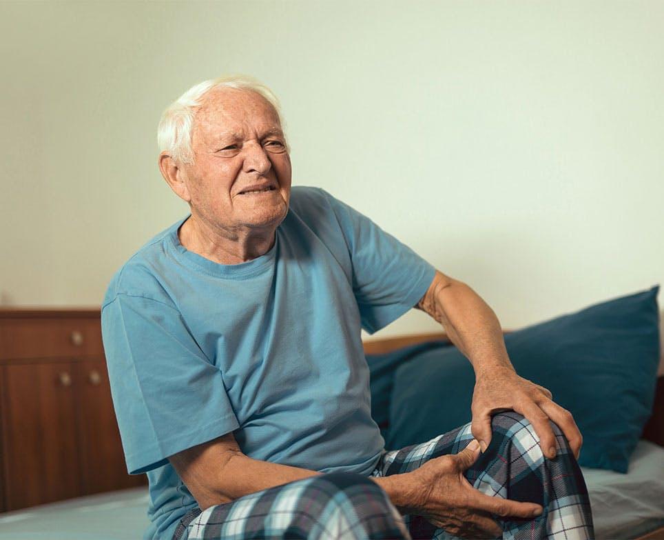 Adulto mayor sujetando su rodilla en señal de dolor.