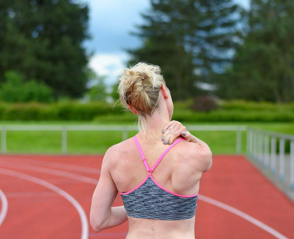 Mujer deportista se toca la aprte de atrás del cuello en señal de dolor.