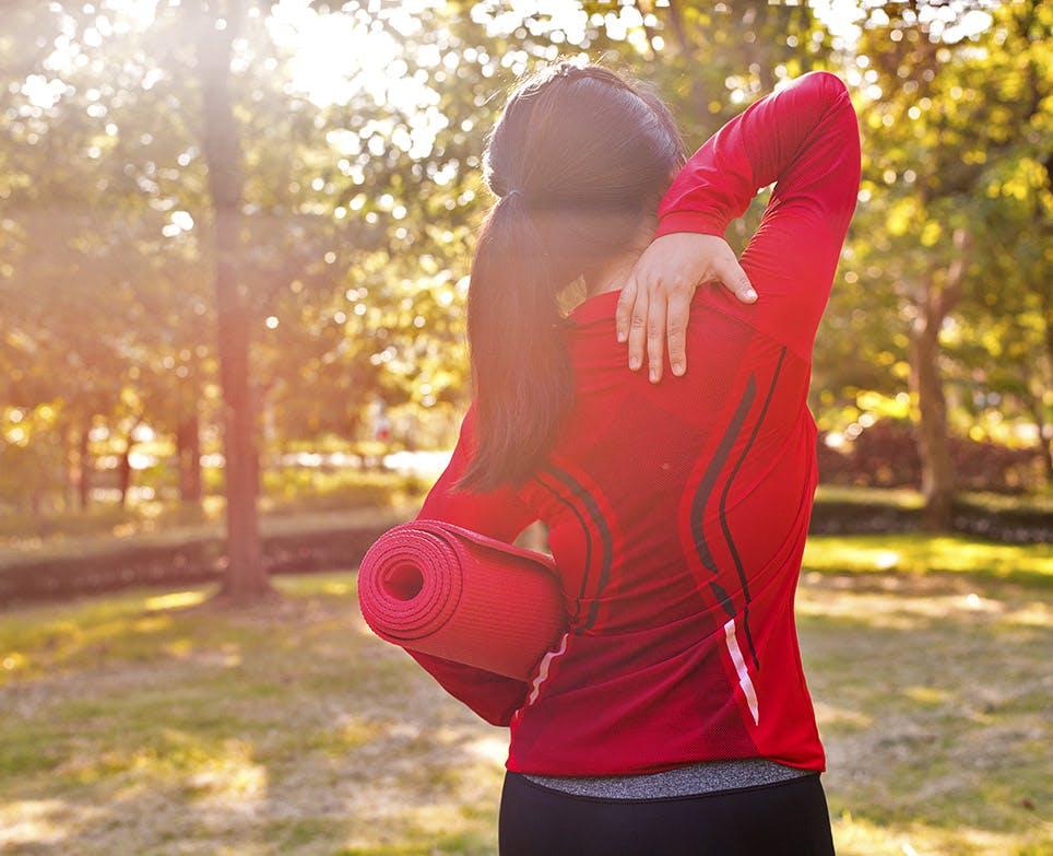 Mujer deportista se toca el homoplato en señal de dolor.