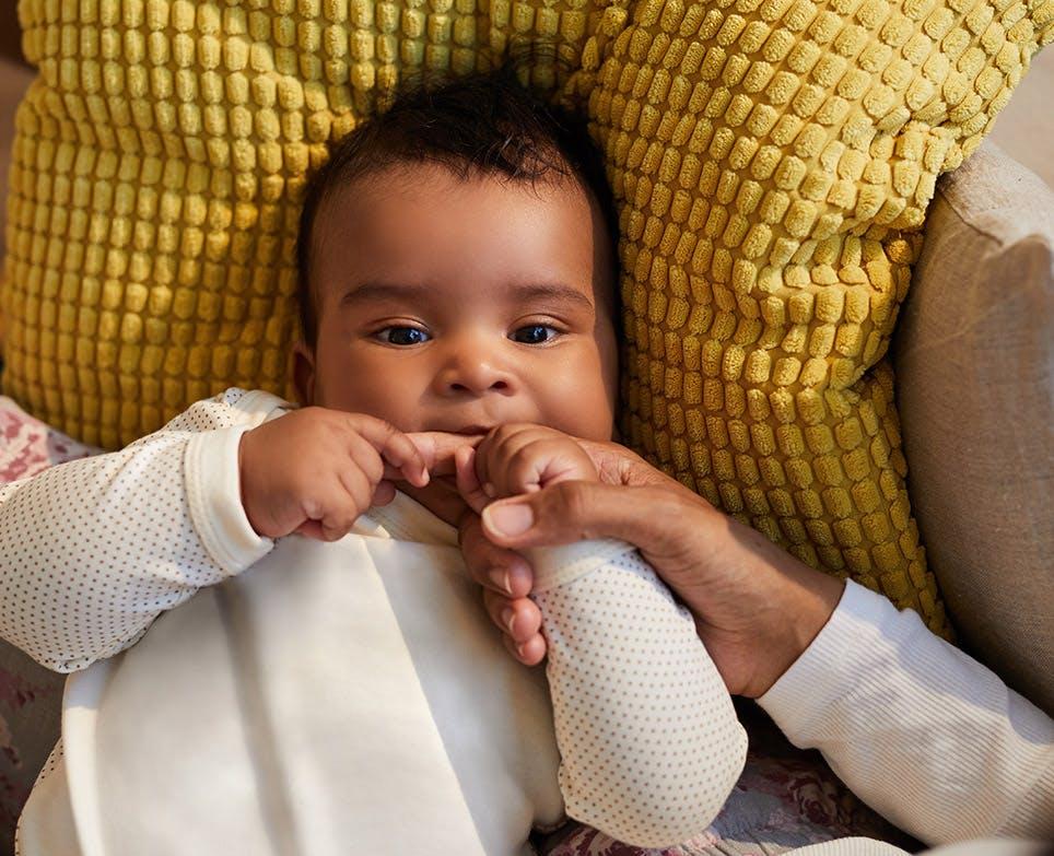 Bebé succionando el dedo de su padre.