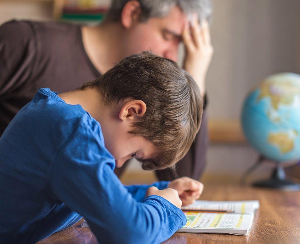 Niño estudiando junto a su padre, con signos de dolor.