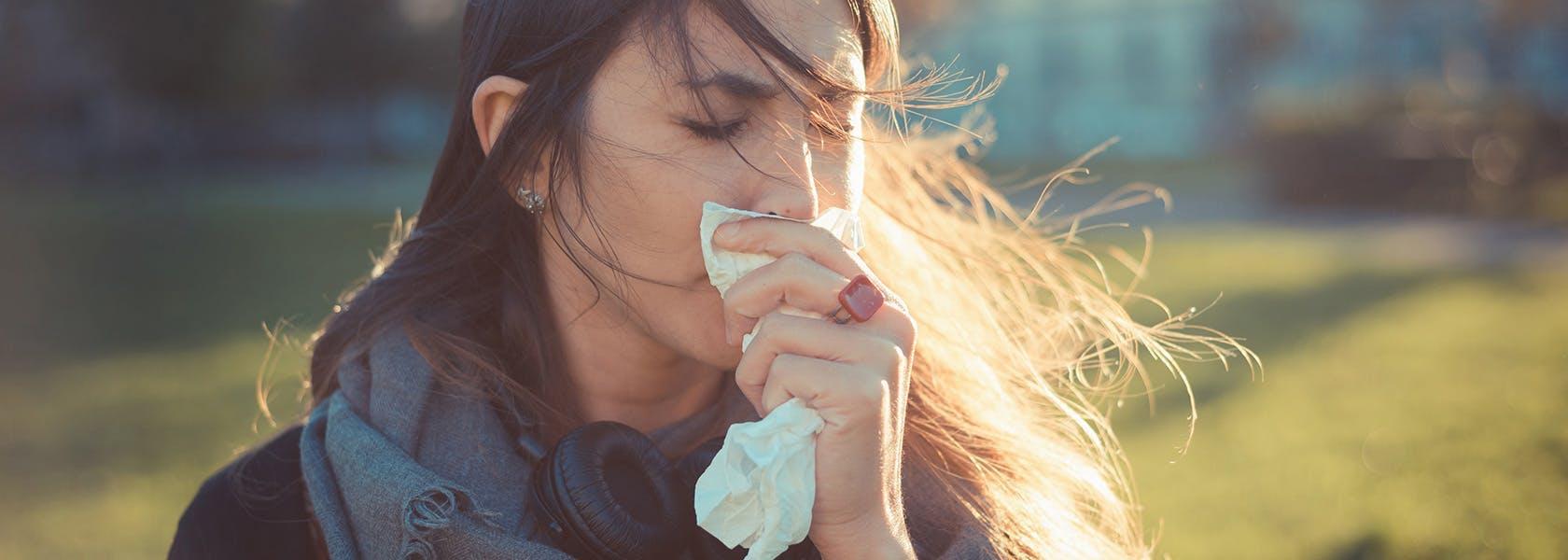 Mujer con congestión nasal limpiando su nariz.