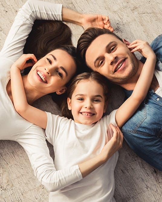 Padres jóvenes recostados con su hija