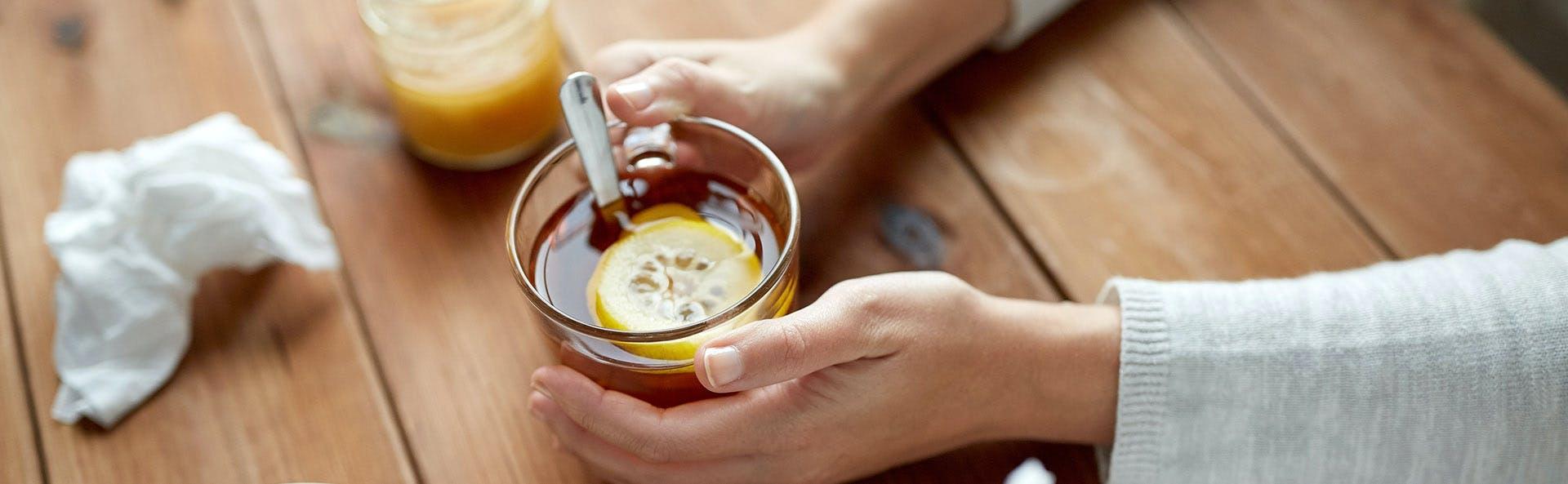 Manos de una mujer sosteniendo una bebida.