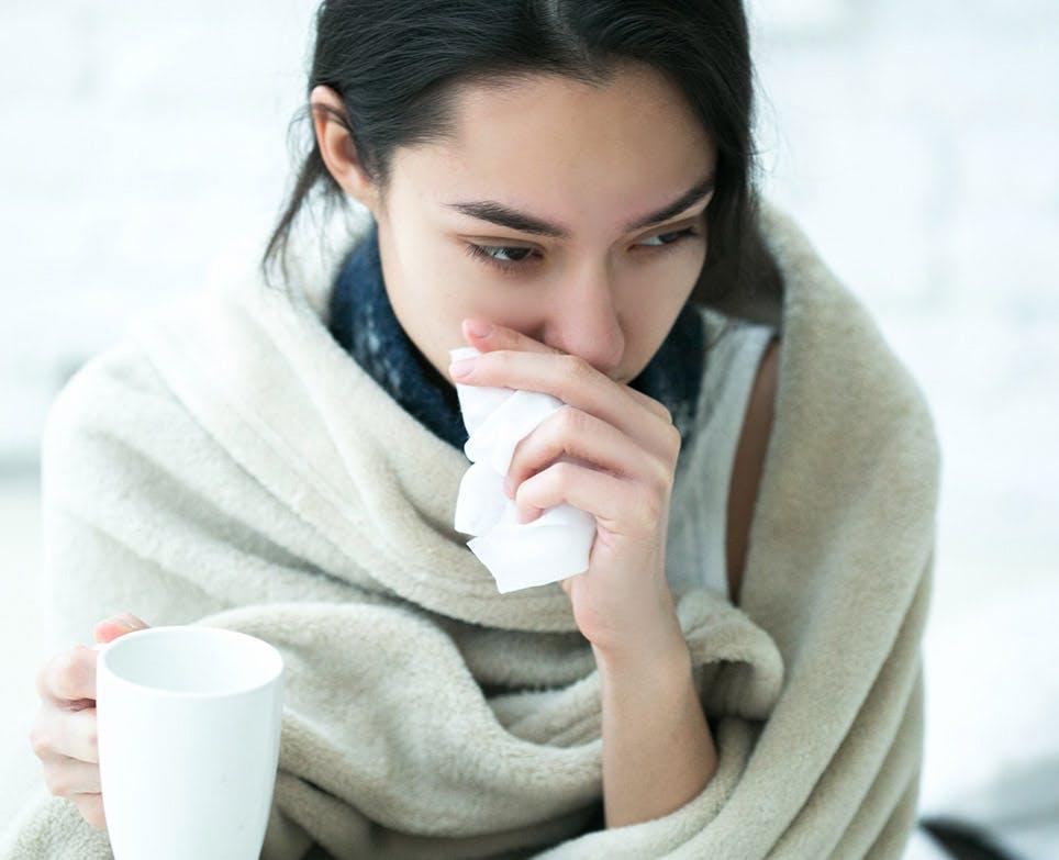Mujer joven limpiando su nariz con un pañuelo.