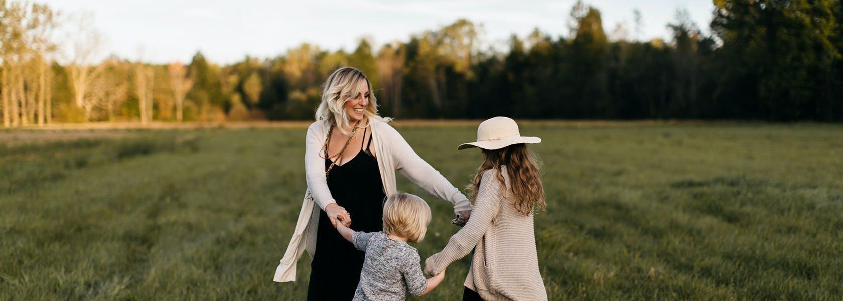 Mor og børn ler og danser sammen i ring