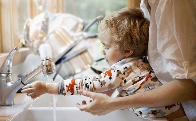 Mor hjælper søn med at vaske hænder
