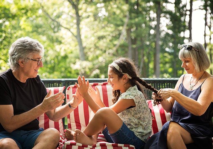 Bedsteforældre leger og fletter hår på deres barnebarn