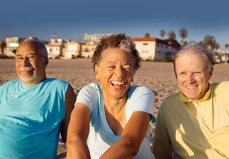 Tre ældre voksne slapper af og ler på stranden