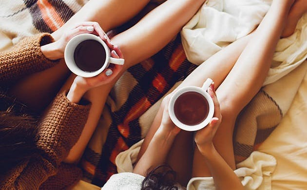 To søstre sidder i hjemmestrikkede sweatre i soveværelse og drikker the