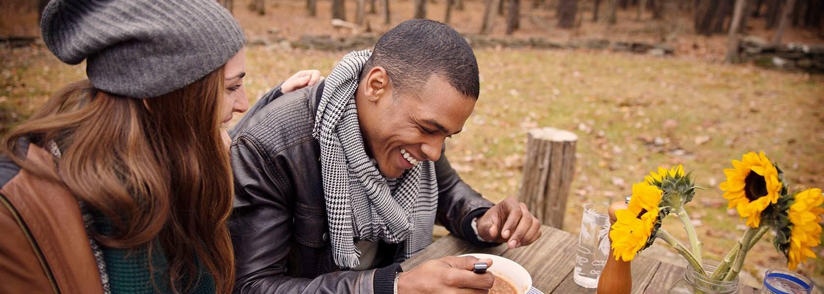 Forkølet mand sidder og drikker suppe
