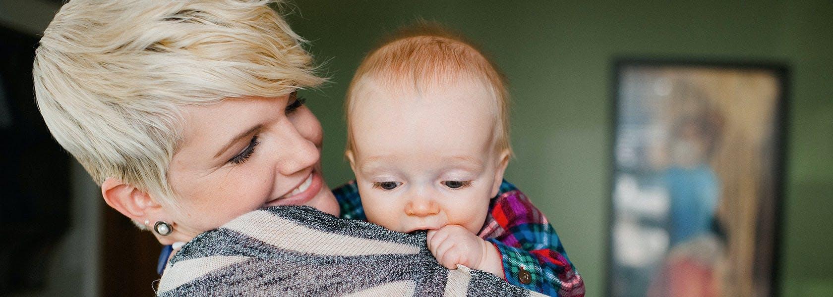 Baby trækker mors trøje op mod munden