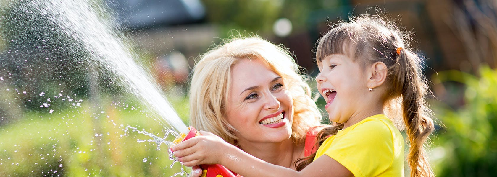 Mor og datter griner og sprøjter vand med vandslange