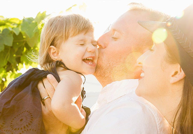 Forældre kæler og kysser deres datter