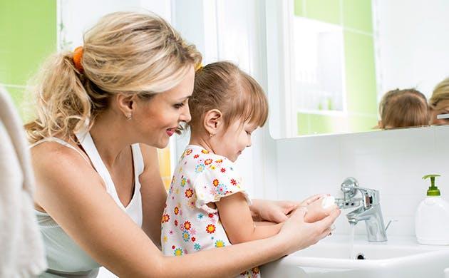 Et barn vasker hænder sammen med sin mor