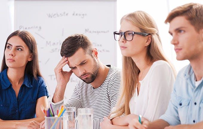 Mand har hovedpine midt i et møde
