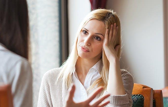 Kvinde har hovedpine og holder om sit hoved