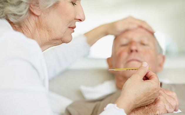 Ældre kvinde hygger om sin mand, der har feber
