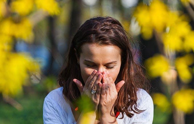 Kvinde har hænderne om munden og nyser