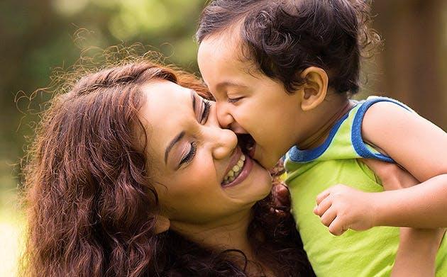 Glad lille dreng kysser sin mor udenfor