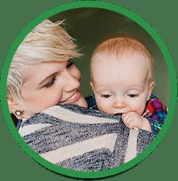 Baby løfter mors trøje op mod munden