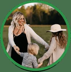 Mor og børn ler og danser i ring