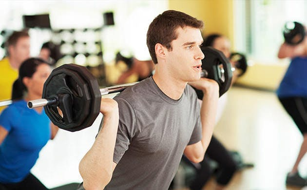 Man Rising From A Squat In A Strength Training Class