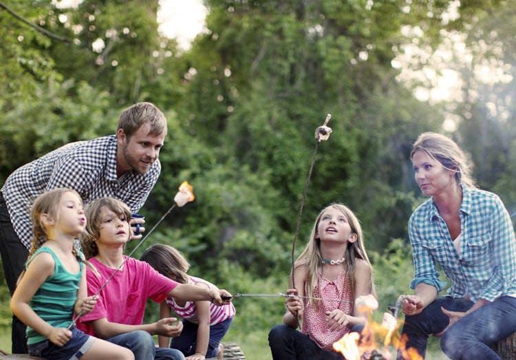 Family Roasting Marshmallows Over Campfire