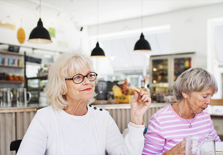 Two elderly woman having coffee together