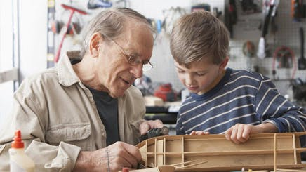 Caucasian Man And Grandson Working On Model Ship